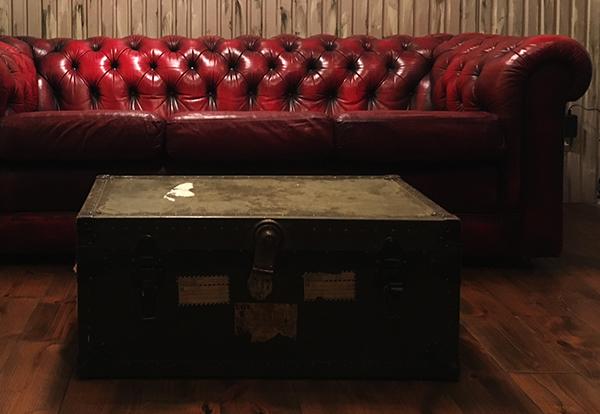 ダークブラウンの床と赤のソファ