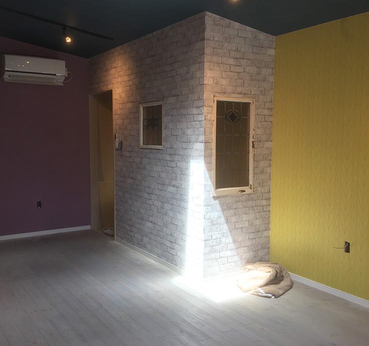 グレーの床に赤紫と黄色の壁紙クロス
